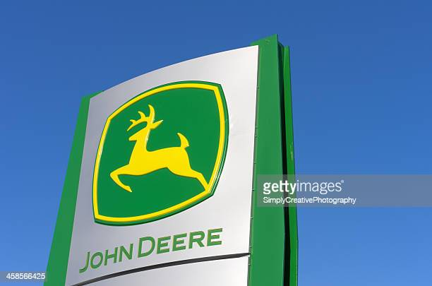 john deere sign against blue sky - john deere stock pictures, royalty-free photos & images