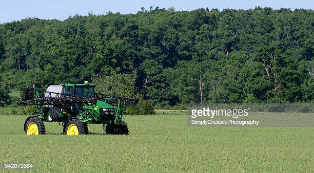 john deere sprayer in field of wheat - john deere stock pictures, royalty-free photos & images