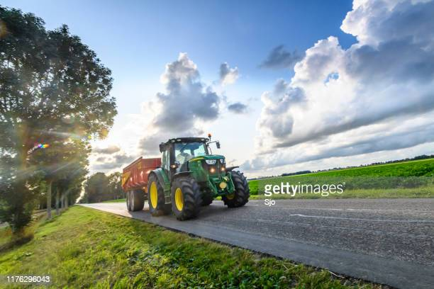 john deere tractor hauling a tipper trailer on a country road in between agricultural fields - rural scene stock pictures, royalty-free photos & images