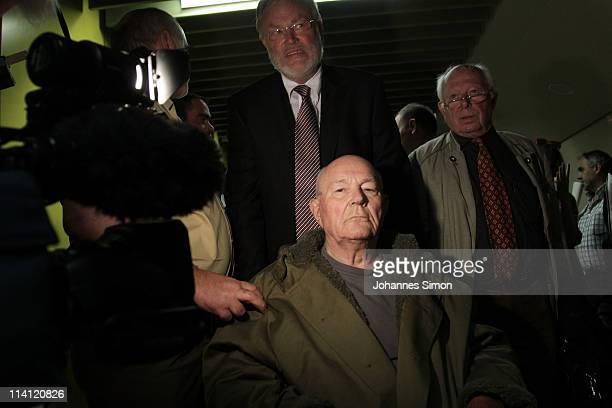 John Demjanjuk and his lawyers Ulrich Busch and Guenther Maull emerge from a Munich court after a judge sentenced him to 5 years in prison for...