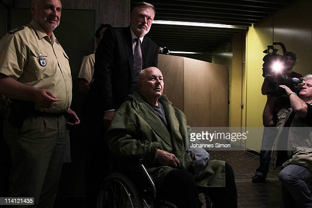 John Demjanjuk and his lawyers Ulrich Busch emerge from a Munich court after a judge sentenced him to 5 years in prison for charges related to 28060...