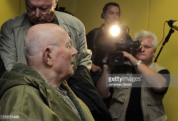 John Demjanjuk emerges from a Munich court after a judge sentenced him to 5 years in prison for charges related to 28060 counts of accessory to...
