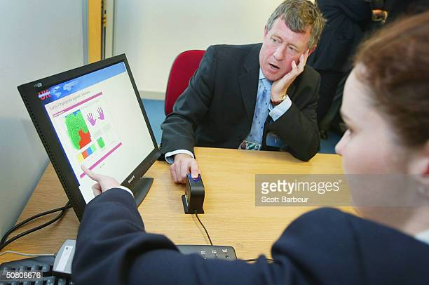 John Denham the chairman of Britain's Home Affairs Select Committee looks at a computer screen displaying information after he had his fingerprint...