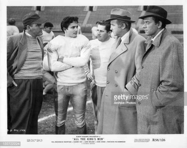 John Derek and Broderick Crawford standing on a football field in a scene from the film 'All The Kings Men', 1949.
