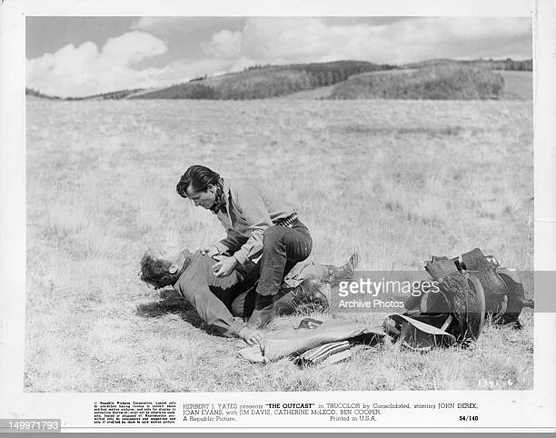John Derek grabbing downed man in the field in a scene from the film 'The Outcast', 1954.