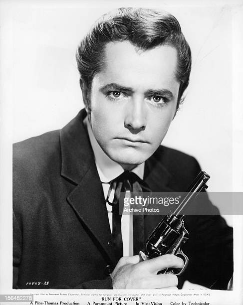 John Derek holds a revolver in publicity portrait for the film 'Run For Cover' 1955