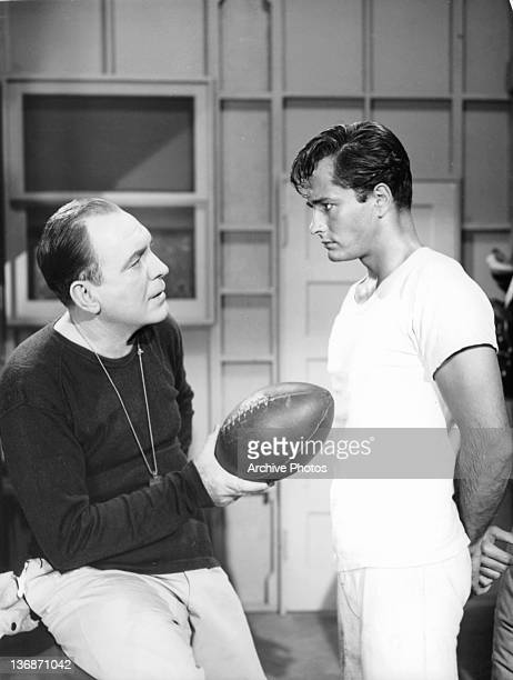 John Derek listening to an unknown actor that is holding a football in a scene from the film 'Saturday's Hero' 1951