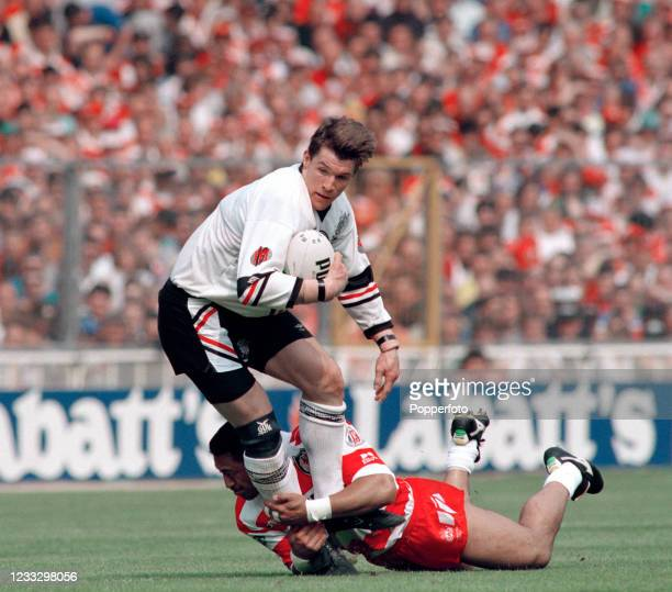 John Devereux of Widnes is tackled by Sam Panapa of Wigan during the Silk Cut Challenge Cup Final at Wembley Stadium on May 1, 1993 in London,...