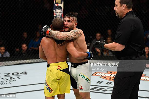 John Dodson and John Lineker of Brazil embrace after going five rounds in their bantamweight bout during the UFC Fight Night event at the Moda Center...