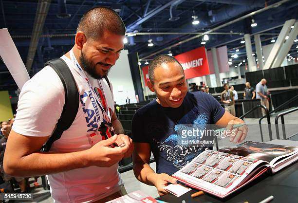 John Dodson signs an autograph for a fan during day 3 of the UFC Expo at the Las Vegas Convention Center on July 10 2016 in Las Vegas Nevada