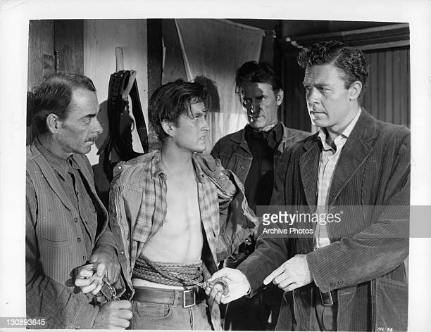John Drew Barrymore tied up surrounded by unidentified men in a scene from the film 'High Lonesome' 1950