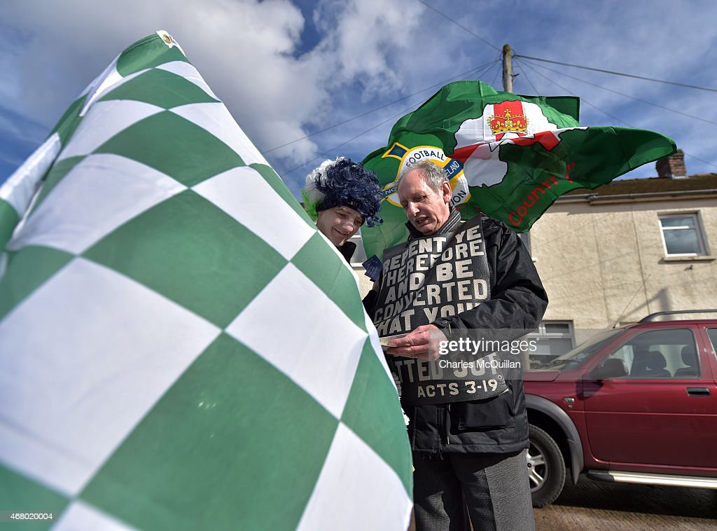 John Dumigan (L) hands out religious tracts against the backdrop of a George Best mural as the Evangelical Protestant Society hold a protest against football on a Sunday before the EURO 2016 Group F qualifier between Northern Ireland and Finland at Windsor Park on March 29, 2015 in Belfast, Northern Ireland. Today's game is the first professional game to take place on a Sunday in Northern Ireland.