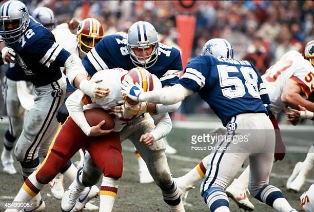 John Dutton and Mike Higman of the Dallas Cowboys tackles John Riggins of the Washington Redskins during an NFL Football game circa 1982 at RFK...