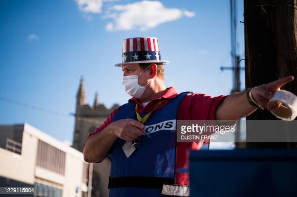 John Eddy gestures as he collects absentee ballots from voters as they drive past the Cuyahoga County Board of Elections in Cleveland, Ohio on...
