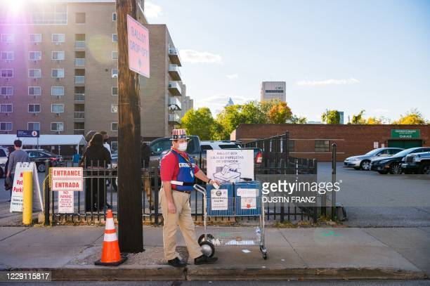 John Eddy stands near a ballot box as he waits to collect absentee ballots from voters as they drive past the Cuyahoga County Board of Elections in...