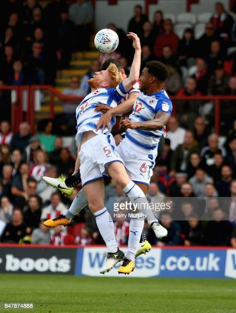 John Egan of Brentford battles for possession with Paul McShane and Liam Moore of Reading during the Sky Bet Championship match between Brentford and...