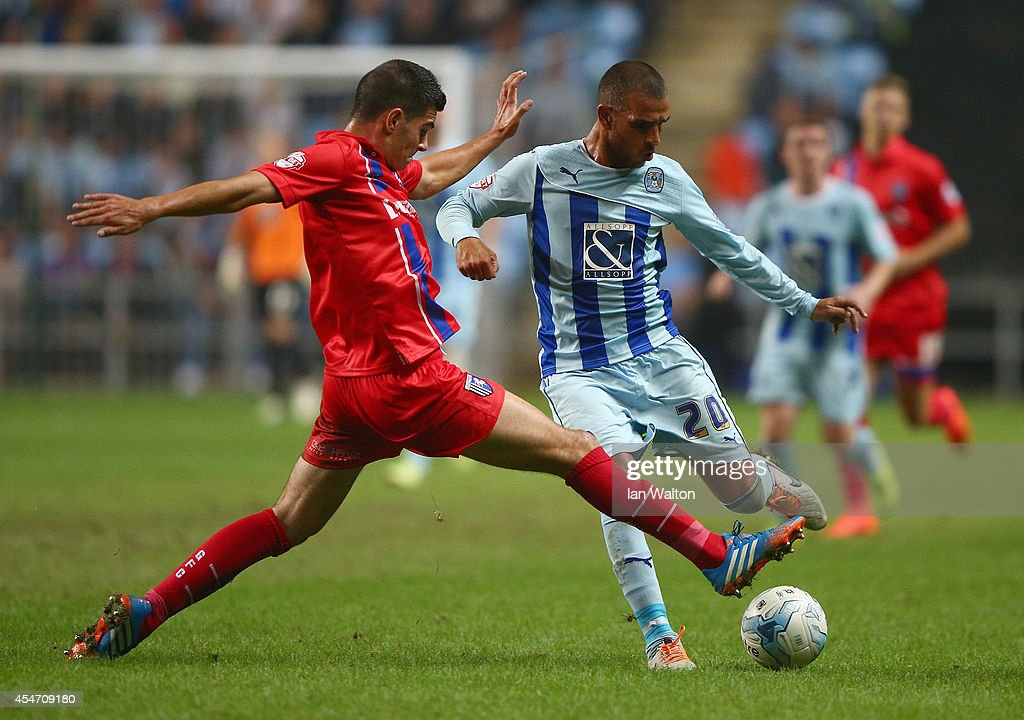 John Egan (L) of Gillingham tries to tackle Marcus Tudgay of Coventry City during the Sky Bet League One match between Coventry City and Gillingham at Ricoh Arena on September 5, 2014 in Coventry, England.