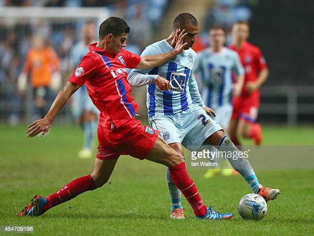 John Egan of Gillingham tries to tackle Marcus Tudgay of Coventry City during the Sky Bet League One match between Coventry City and Gillingham at...