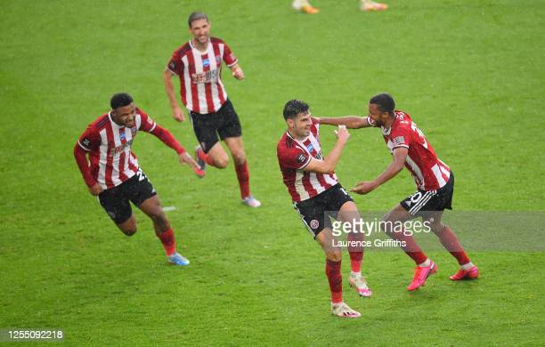 John Egan of Sheffield United celebrates with Lys Mousset and Richairo Zivkovic after scoring the winning goal during the Premier League match...
