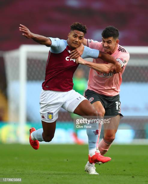 John Egan of Sheffield United holds back Ollie Watkins of Aston Villa and is later shown a red card during the Premier League match between Aston...