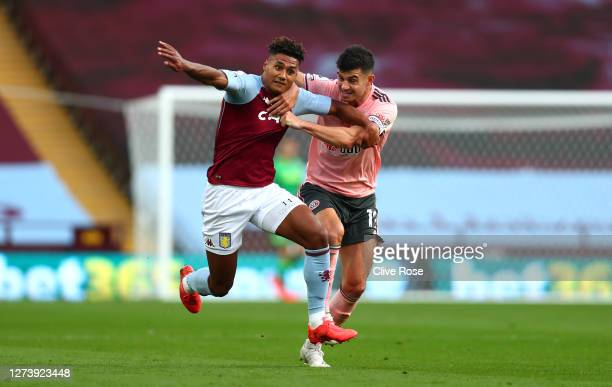 John Egan of Sheffield United holds back Ollie Watkins of Aston Villa and is later shown a red card following a VAR review during the Premier League...