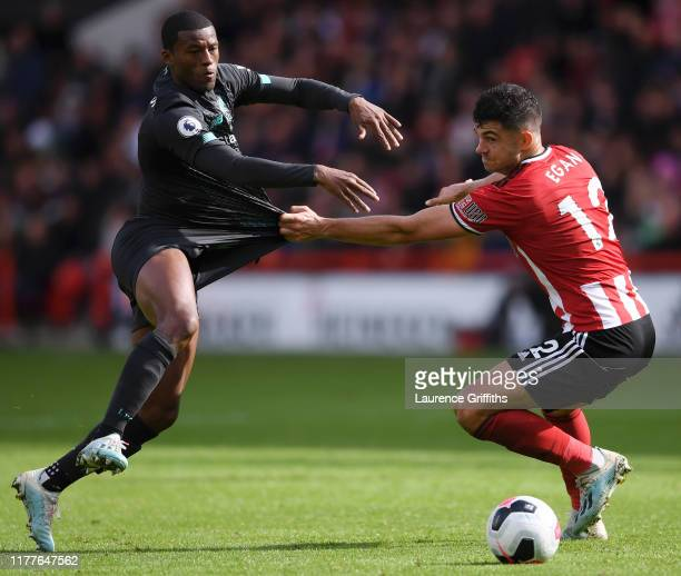 John Egan of Sheffield United is challenged by Georginio Wijnaldum of Liverpool during the Premier League match between Sheffield United and...