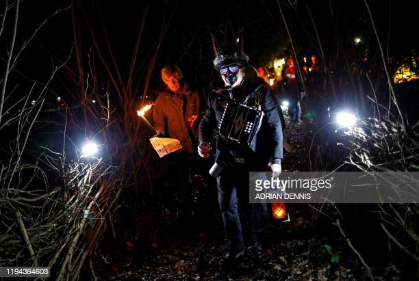 John Ellis the Bagman for the Hook Eagle Morris Men walks to the orchard with a villager to play music and sing during the annual Wassail night in...