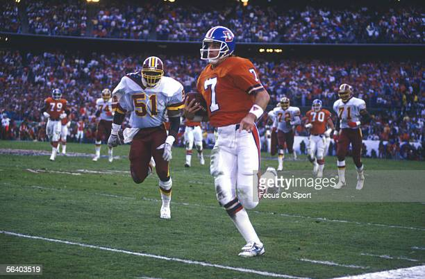 John Elway of the Denver Broncos carries the ball near the sidelines during Super Bowl XXII against the Washington Redskins on January 31 1988 in San...