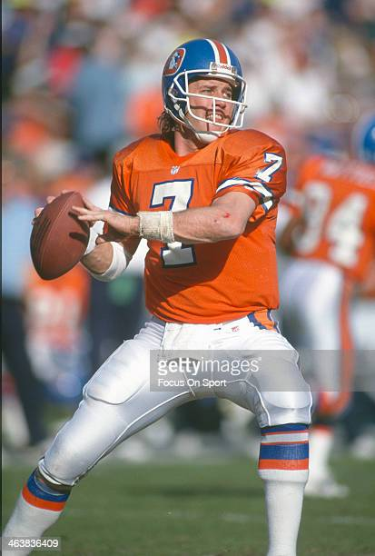John Elway of the Denver Broncos drops to pass during an NFL football game circa 1991 at Mile High Stadium in Denver Colorado Elway played for the...