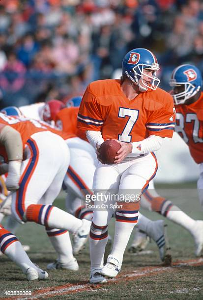 John Elway of the Denver Broncos turns to hand the ball off against the Kansas City Chiefs during an NFL football game December 14 1985 at Mile High...