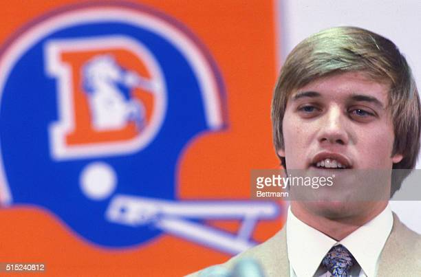 John Elway picked by Broncos in NFL draft standing alone at a press conference with the Denver Broncos Logo in the background