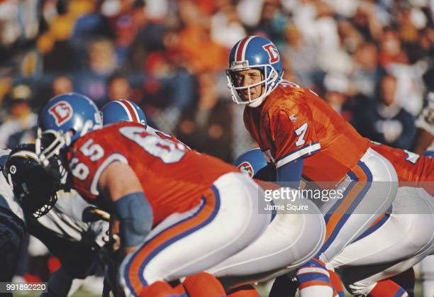 John Elway, Quarterback for the Denver Broncos calls the play on the line of scrimmage during the American Football Conference West game against the...