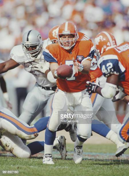 John Elway, Quarterback for the Denver Broncos hands the ball off to his running back Leonard Russell during the American Football Conference West...