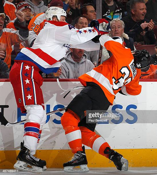 John Erskine of the Washington Capitals cross checks Zac Rinaldo of the Philadelphia Flyers during the second period of an NHL hockey game at Wells...
