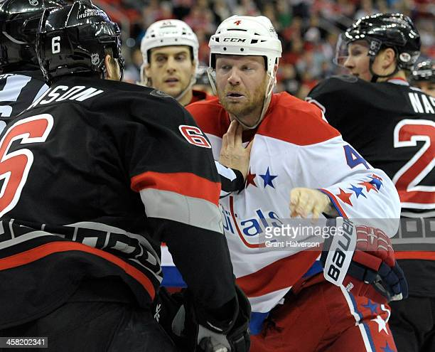 John Erskine of the Washington Capitals drops his glove as he prepares to fight Tim Gleason of the Carolina Hurricanes during their game at PNC Arena...