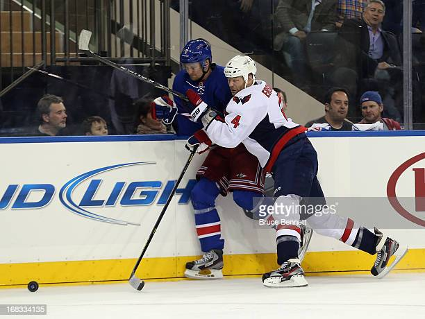 John Erskine of the Washington Capitals hits Anton Stralman of the New York Rangers into the boards in Game Four of the Eastern Conference...