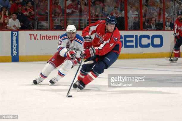 John Erskine of the Washington Capitals skates with the puck while Nikolai Zherdev chases him from behind during Game Five of the Eastern Conference...