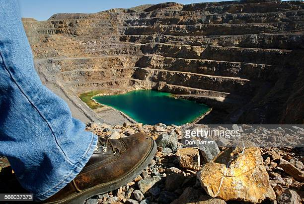 PASS CA John Espinoza looks down on ground water that has accumulated in the pit of the Mountain Pass rare earth mine Green sediment in the shallow...