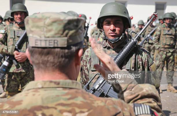 John Etter from Fort Smith, Arkansas with the U.S. Army's 130th Engineer Brigade salutes a graduating Afghan National Army soldier while...