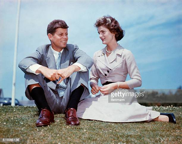 John F Kennedy and Jacqueline Bouvier sit together in the sunshine at Kennedy's family home at Hyannis Port Massachusetts a few months before their...