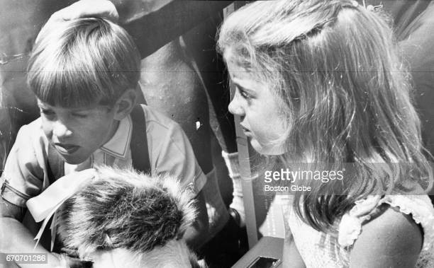 John F Kennedy Jr and his sister Caroline Kennedy sit together at Cardinal Richard Cushing's 70th birthday party in Boston on Aug 24 1965