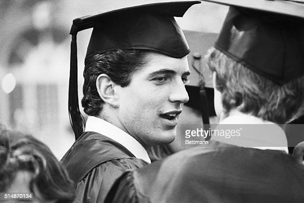 John F Kennedy Jr chats with a classmate at his graduation ceremony at Brown University where he received a Bachelors of Arts in History