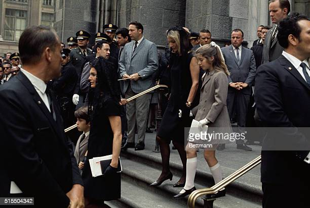 John F Kennedy Jr clings to his mother Jacqueline Kennedy as they leave St Patrick's Cathedral June 8th following the Requiem Mass for Mrs Kennedy's...