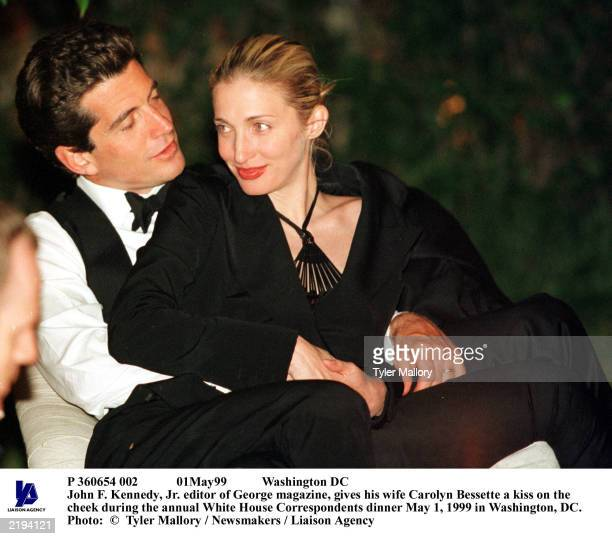 John F Kennedy Jr editor of George magazine sits with his wife Carolyn Bessette on his lap during the annual White House Correspondents dinner in...