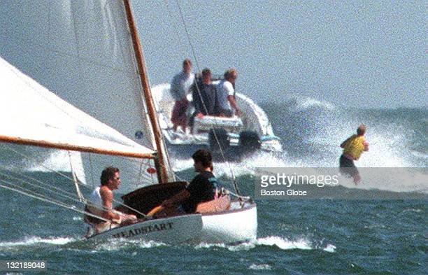 John F Kennedy Jr left sails with relatives as Congressman Joe Kennedy far right in powerboat is at the wheel of his powerboat as he pulls a...