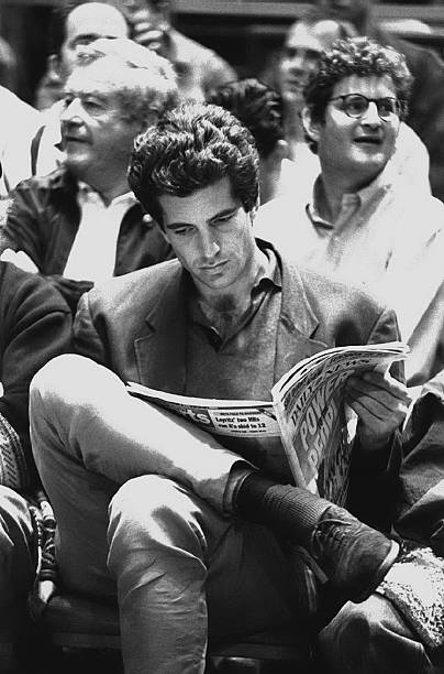 John F. Kennedy Jr. peruses the Daily News during a quiet mo
