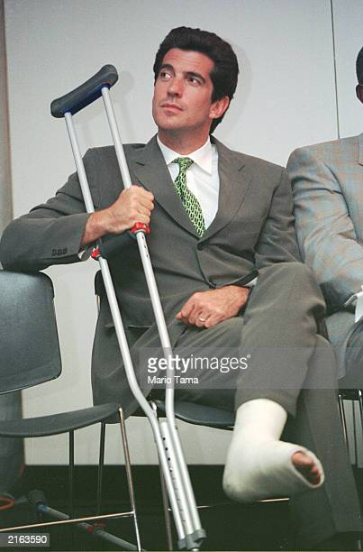 John F Kennedy Jr sits with his leg in a cast at the George Magazine Politicians vs Pundits auto race held at the US Air Arena June 15 1999 in...