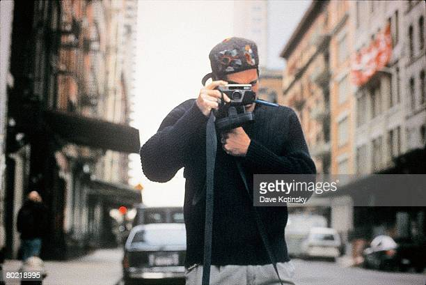 John F Kennedy Jr takes a photo in front of his Tribeca apartment in October 1996 in New York New York