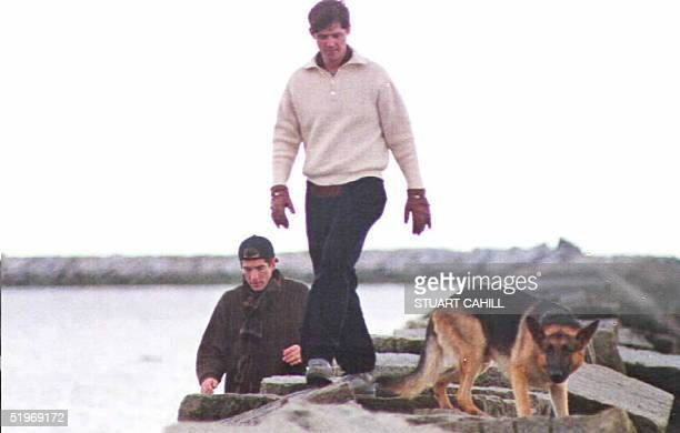 John F Kennedy Jr William Kennedy Smith and JFK Jr's dog Sampson walk along a breakwater on the family compound in Hyannisport 23 January The Kennedy...