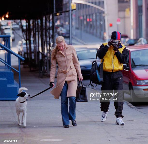 John F. Kennedy Junior and wife Carolyn Bessette and dog take a stroll in Tribeca. John takes photos with a Leica camera of the photographers.